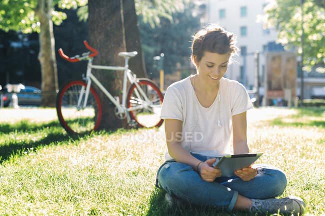 Sorridente giovane donna seduta sul prato utilizzando tablet digitale — Foto stock