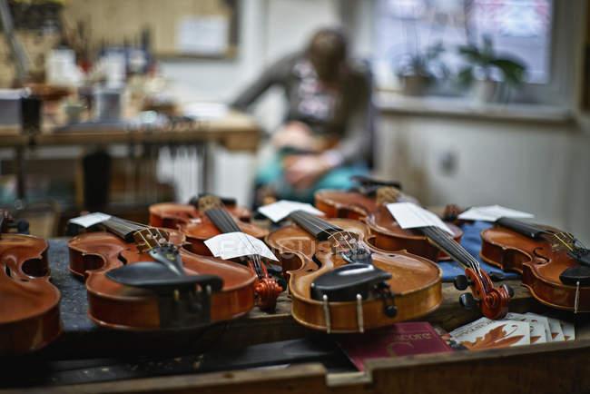 Geigen auf dem Schreibtisch zur Reparatur in der Werkstatt des Geigenbauers — Stockfoto