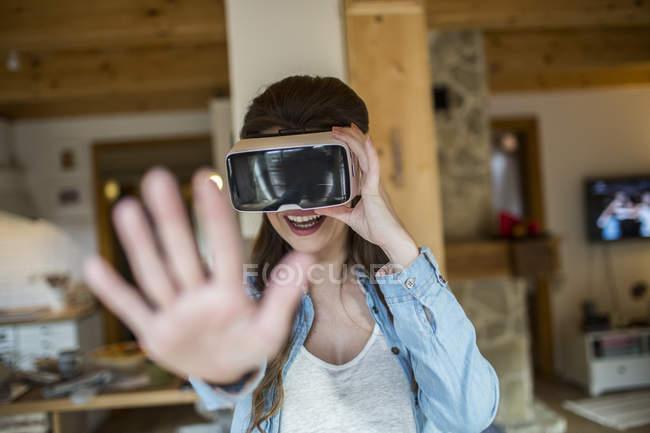 Jeune femme à la maison utilisant des lunettes de réalité virtuelle — Photo de stock