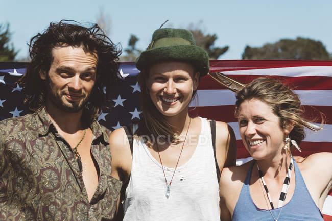 Портрет трёх улыбающихся хиппи с флагом США — стоковое фото
