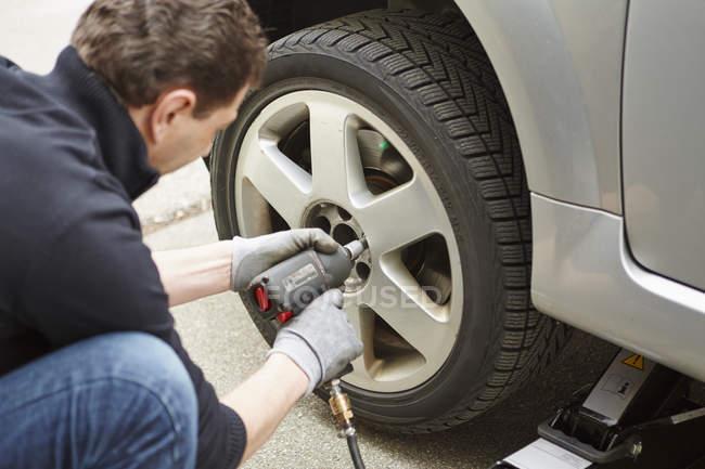 Mature man changing car tire — Stock Photo