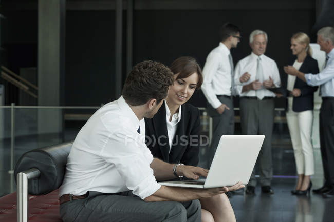 Caucasian businessman and businesswoman with laptop — Stock Photo