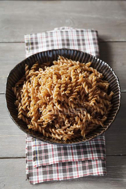 Миску локшини spelt цільного зерна і полотнище на дерев'яну столову — стокове фото