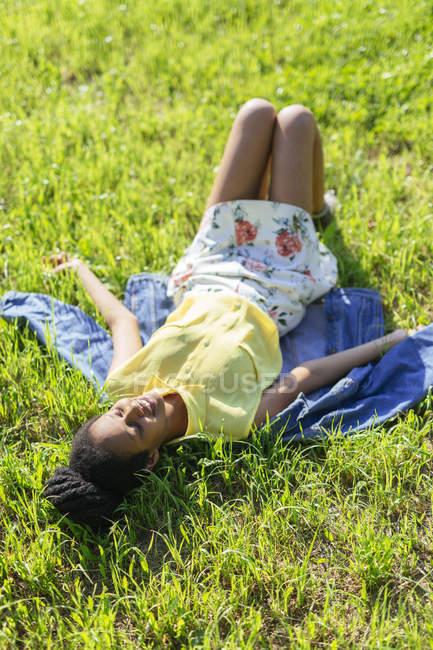 Jeune femme se relaxant sur une prairie — Photo de stock