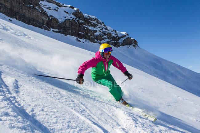 Женщина, катания на снежных горном склоне в ярких Горнолыжная одежда для, шлем и googles — стоковое фото