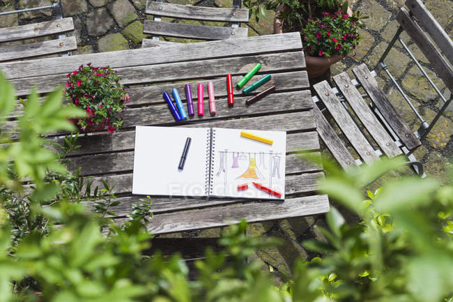 Drawing, sketch book with woman's drawing and coloring pencils on wooden garden table — Stock Photo