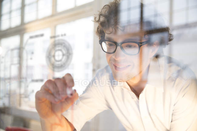 Portrait of young architect fastening construction plan on glass pane in office — Stock Photo