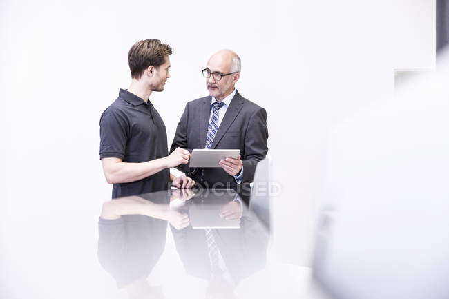 Two man talking holding digital tablet — Stock Photo