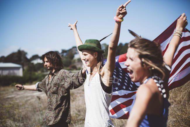 Три аплодирующих хиппи с флагом США в природе — стоковое фото