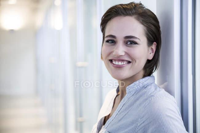 Mulher sorridente em um corredor — Fotografia de Stock