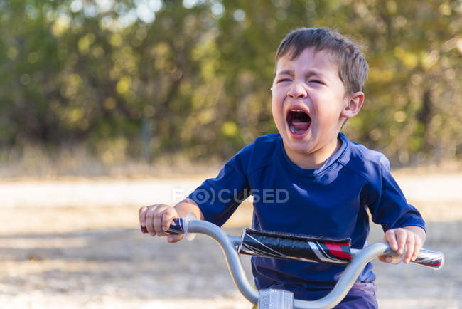 Despaired crying boy on bike in park — Stock Photo