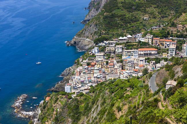 Italia, Liguria, Cinque Terre, Riomaggiore, veduta delle case in collina sull'acqua — Foto stock