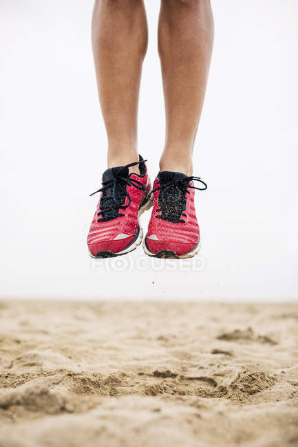 Legs of athlete jumping mid-air in sand on beach — Stock Photo