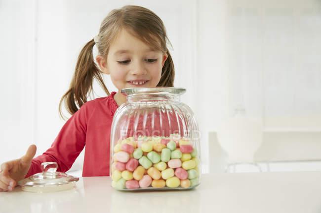 Fille avec bonbons pot regarder à l'intérieur — Photo de stock