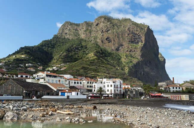 Portugal, Madeira, Porto da Cruz, Porto com edifícios contra rochas — Fotografia de Stock