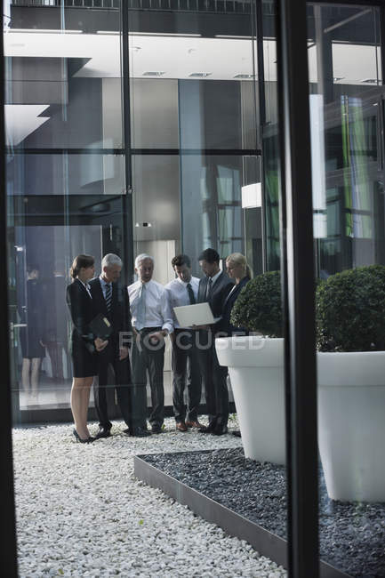 Group of caucasian businesspeople with laptop beside office building — Stock Photo