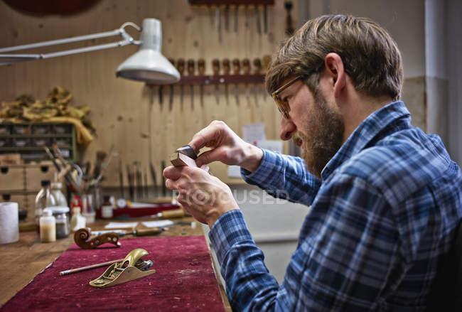 Violin maker examining neck of instrument in workshop — Stock Photo
