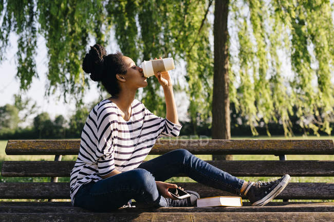 Молодая женщина, сидящая на скамейке в парке и пьющая кофе — стоковое фото