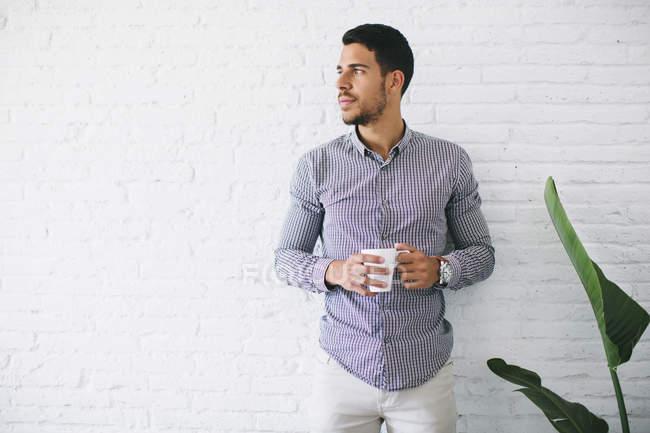 Giovane uomo d'affari in piedi con una tazza di caffè contro muro di mattoni bianchi — Foto stock