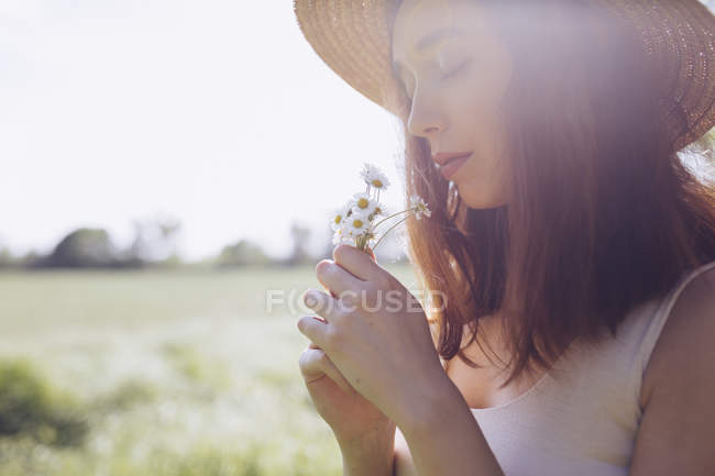 Young woman with daisies at backlight — Stock Photo