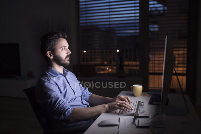 Man working at night, using computer — Stock Photo