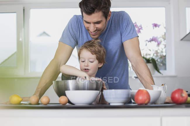 Pai e filho se preparando massa de waffle na cozinha — Fotografia de Stock