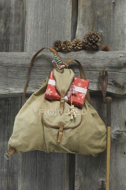 Antigua mochila con regalo de Navidad y la decoración colgante en madera de la pared - foto de stock