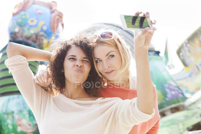 Deux jeunes femmes à la foire en utilisant le téléphone intelligent — Photo de stock