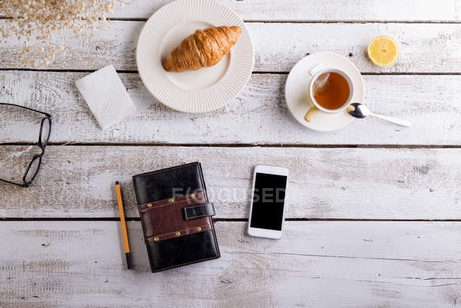 Table with croissant, tea, smart phone and personal organizer — Stock Photo