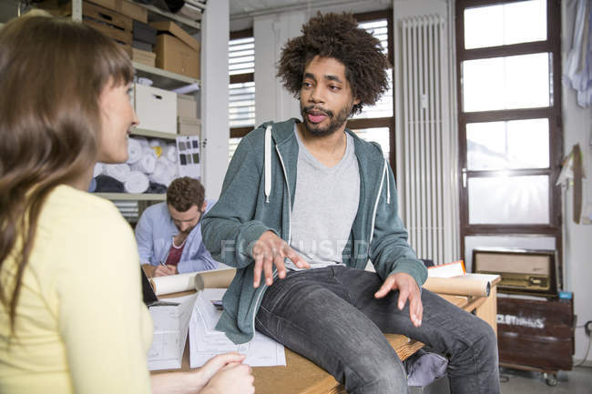 Three creative professionals talking in office — Stock Photo