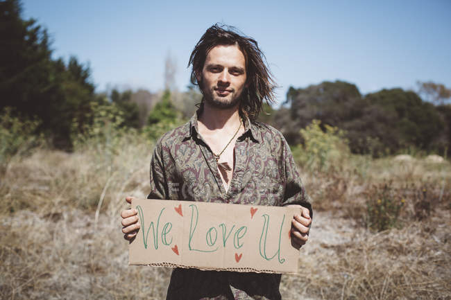 Hippie holding 'We love you' sign in the nature — Stock Photo