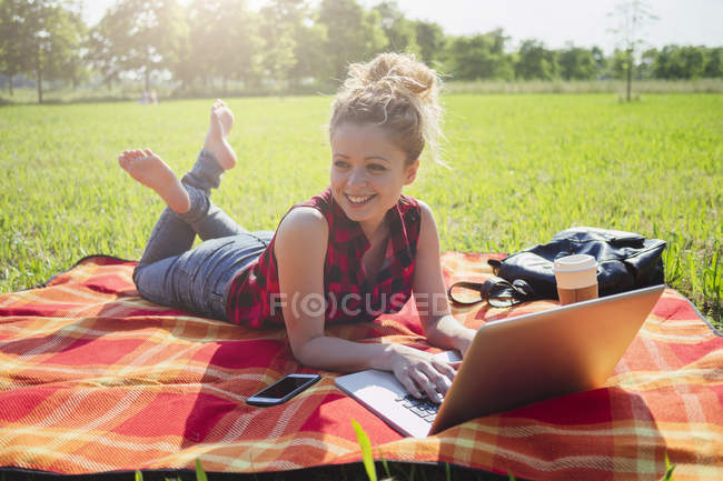 Lächelnde Frau liegt mit Laptop auf Decke auf einer Wiese — Stockfoto