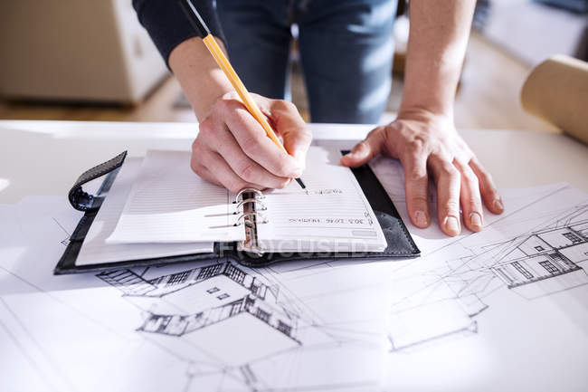 Architect making notes in his personal organizer — Stock Photo