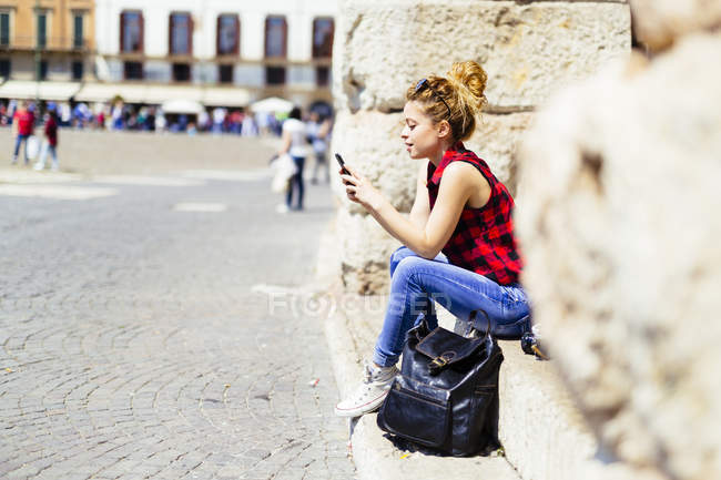 Italy, Verona, woman sitting on stairs looking at cell phone — Stock Photo