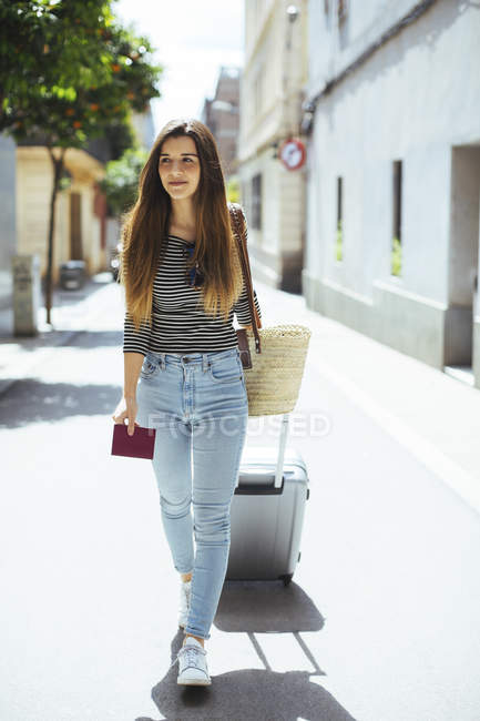 Young woman traveling with wheeled luggage in city — Stock Photo