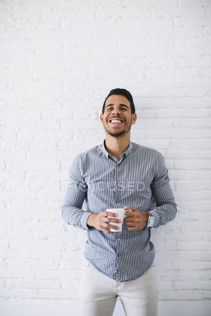 Jovem empresário de pé contra a parede, segurando xícara de café — Fotografia de Stock