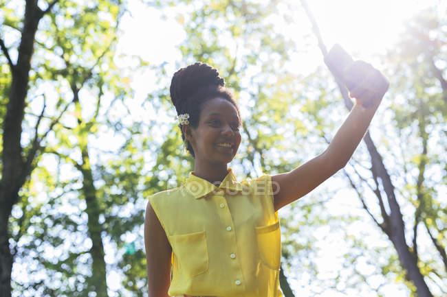 Sourire jeune femme dans la nature prendre selfie avec smartphone — Photo de stock