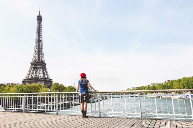 Франция, Париж, вид сзади женщины в красном берете, смотрящей на Эйфелеву башню — стоковое фото