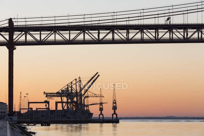 Portugal, Lisbon, View of 25 de Abril Bridge at River Tagus and harbour — Stock Photo