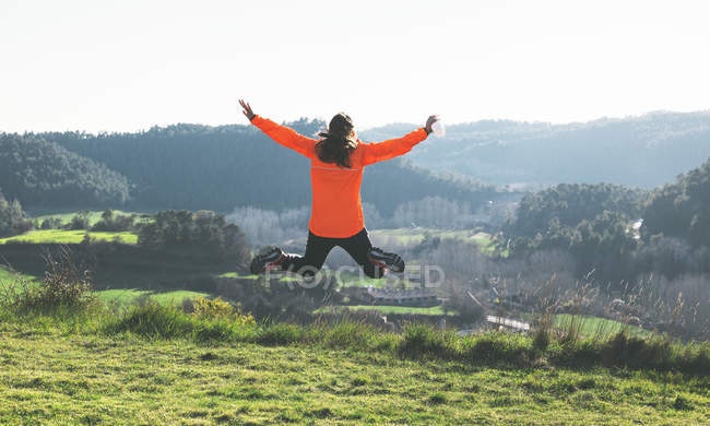 Young female jogger jumping in the air — Stock Photo
