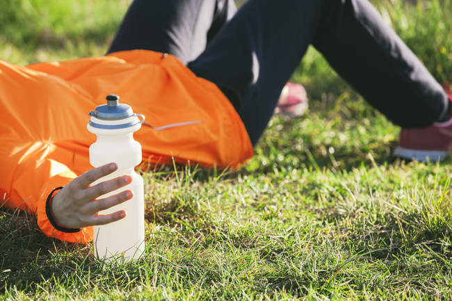 Young female jogger having a break on a meadow — Stock Photo