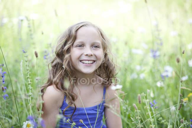 Portrait de fille souriante assise sur la prairie de fleurs — Photo de stock