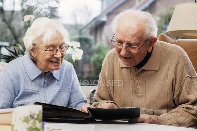 Старшая пара смотрит старые фотографии дома — стоковое фото