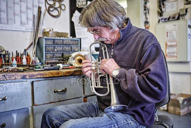 Приборостроитель осматривает трубу в мастерской — стоковое фото