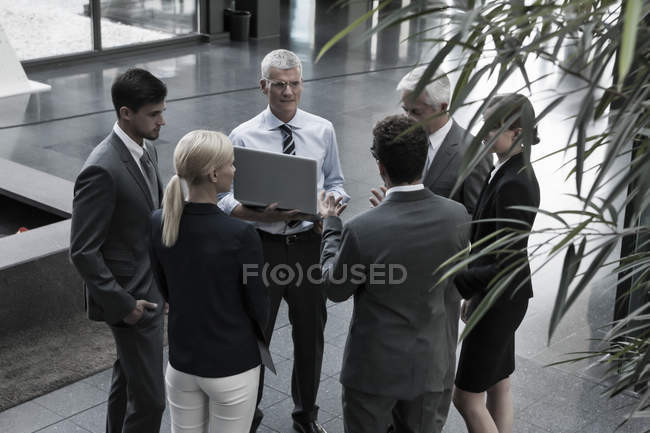 Confident business people with laptop talking in lobby — Stock Photo