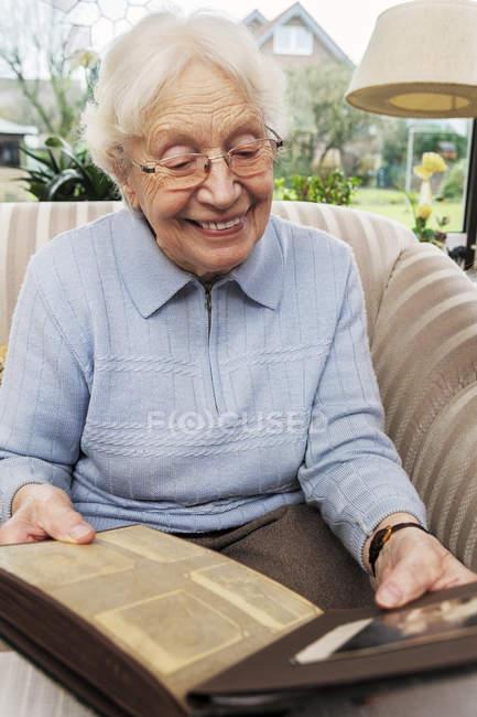 Senior woman watching old photographs at home — Stock Photo