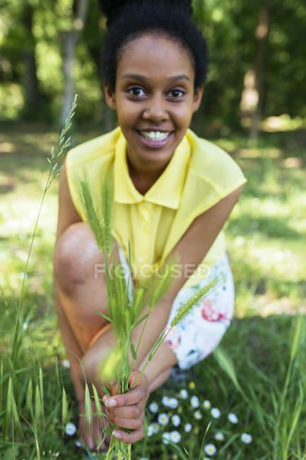 Portrait de jeune femme souriante cueillant des herbes — Photo de stock