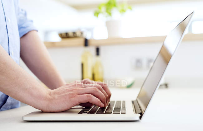 Man working in kitchen using laptop, close up — Stock Photo
