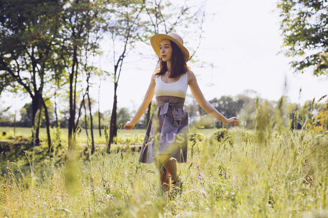 Young woman dancing on a meadow in spring — Stock Photo