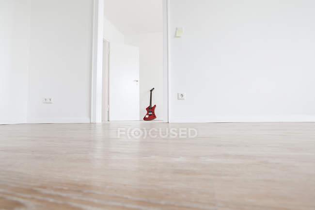Гитара, опирающаяся на стену внутри помещения, на уровне поверхности — стоковое фото